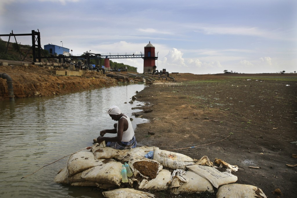 In this Wednesday, July 17, 2019, photo, an Indian fixes bait for fish, sitting on the dried up bed of Red Hills lake, a 4,500-acre 19th-century reser...