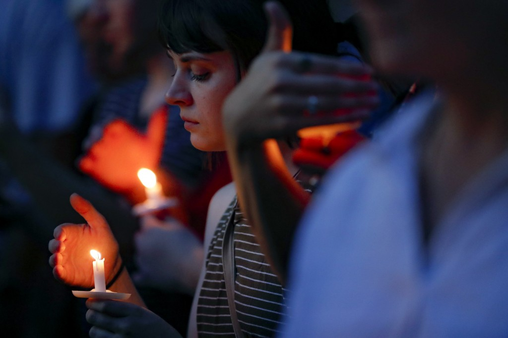 Mourners bow their heads in prayer as they gather for a vigil at the scene of a mass shooting, Sunday, Aug. 4, 2019, in Dayton, Ohio. Multiple people ...