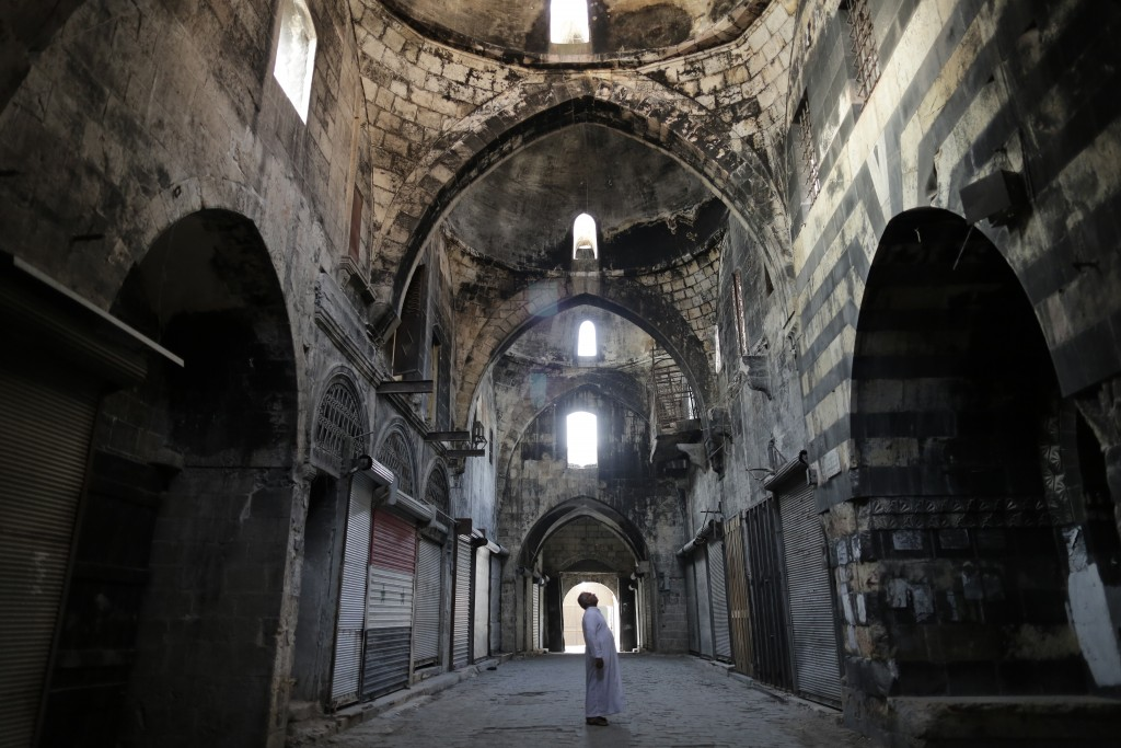In this Saturday, July 27, 2019 photo, a Syrian man checks a market in the old city of Aleppo, Syria. Much of Aleppo's centuries-old covered market is