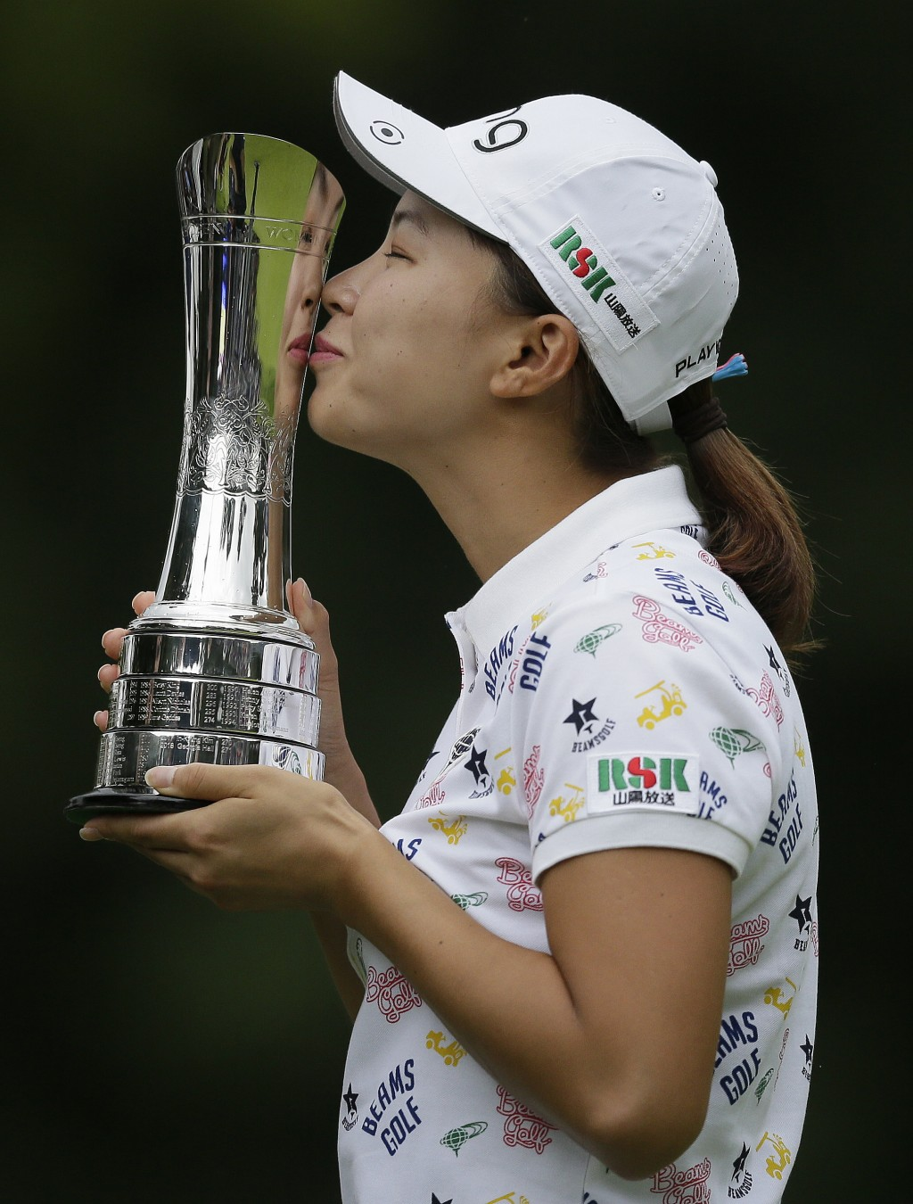 Japan's Hinako Shibuno kisses the trophy as she celebrates after winning the Women's British Open golf championship at Woburn Gold Club near near Milt...