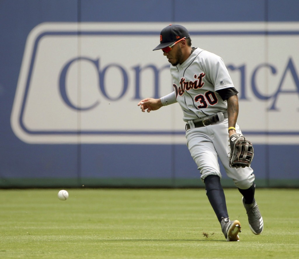 Detroit Tigers center fielder Harold Castro (30) drops the ball after making an out during the first inning of a baseball game against the Texas Range...