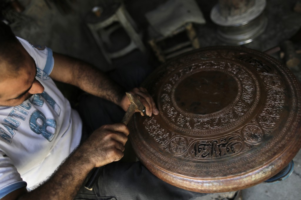 In this Sunday, July 28, 2019 photo, Ahmad Zuhdi Ghazoul works on a piece of copper on the newly renovated copper market in Aleppo, Syria. Much of Ale...