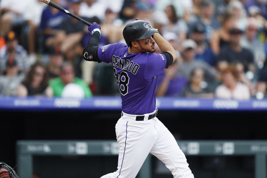 Colorado Rockies' Nolan Arenado follows the flight of his solo home run off San Francisco Giants starting pitcher Andrew Suarez in the fifth inning of...