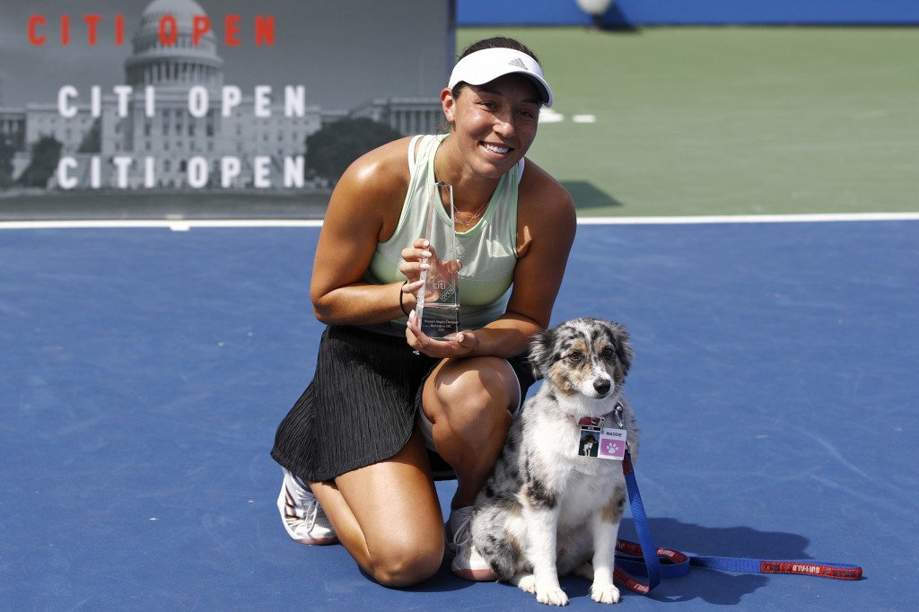 Jessica Pegula poses with a trophy and her dog Maddie after defeating Camila Giorgi, of Italy, in a final match at the Citi Open tennis tournament, Su