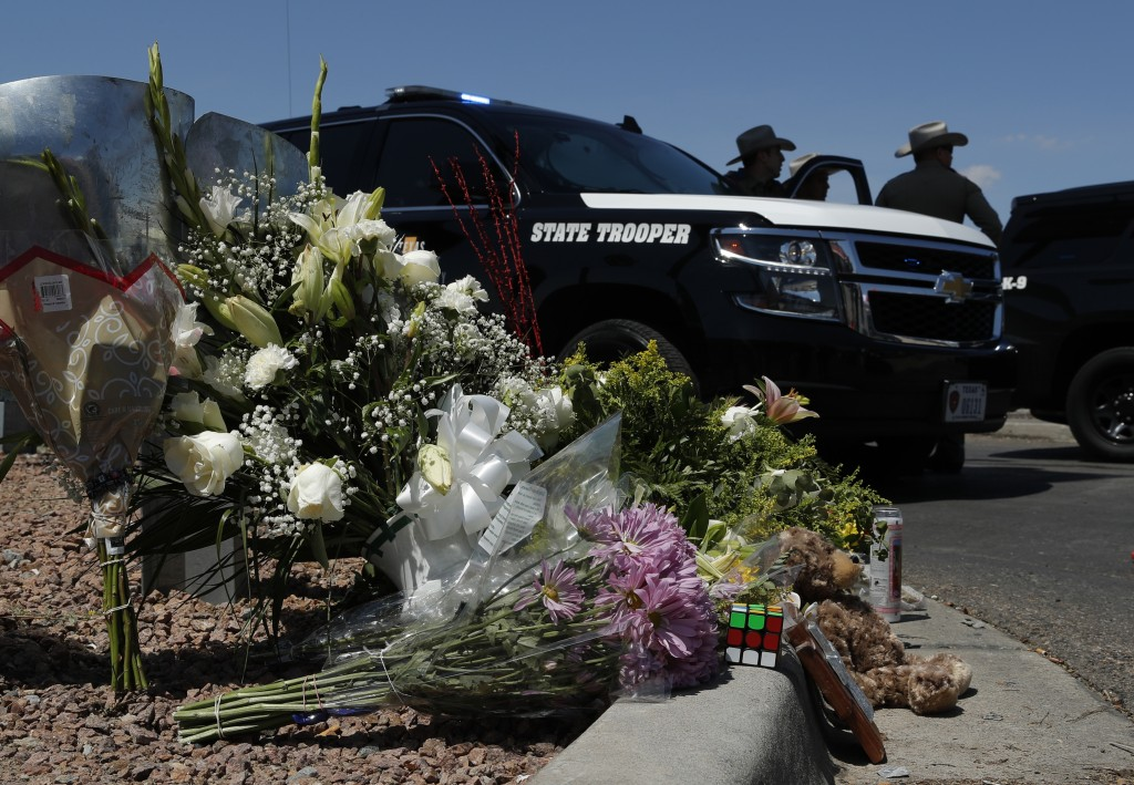 Flowers adorn a makeshift memorial near the scene of a mass shooting at a shopping complex Sunday, Aug. 4, 2019, in El Paso, Texas. (AP Photo/John Loc...