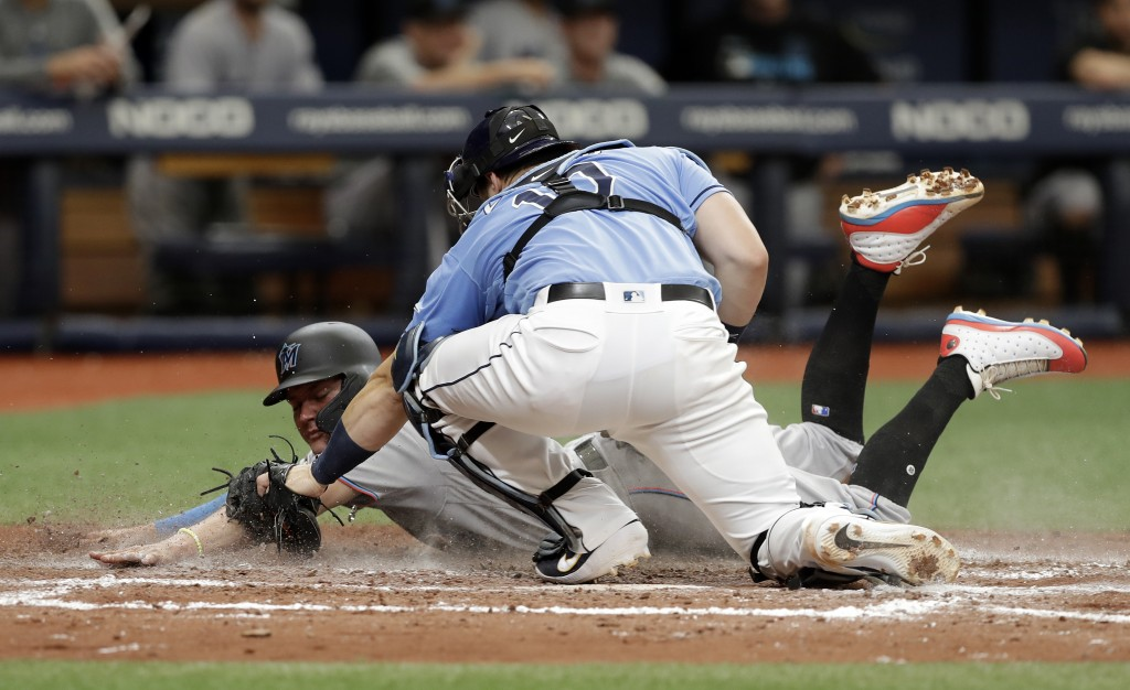 Tampa Bay Rays catcher Mike Zunino (10) tags out Miami Marlins' Miguel Rojas who was attempting to steal home plate during the sixth inning of a baseb...