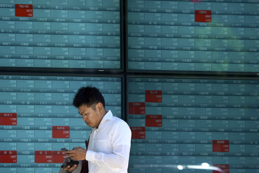 A man walks past an electronic stock board showing Japan's stock prices at a securities firm in Tokyo Monday, Aug. 5, 2019. Asian stock markets fell f