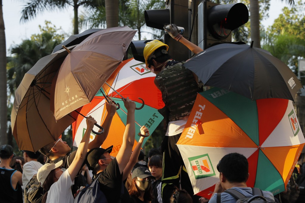 Protesters using umbrellas to cover themselves as they spray a set of traffic lights during the anti-extradition bill protest destination in Hong Kong...