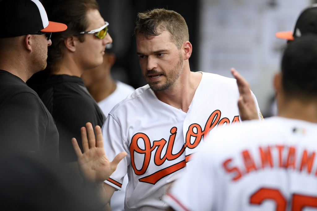Baltimore Orioles' Trey Mancini reacts in the dugout after he scored on a bases-loaded walk to teammate Chance Sisco during the fifth inning of a base...