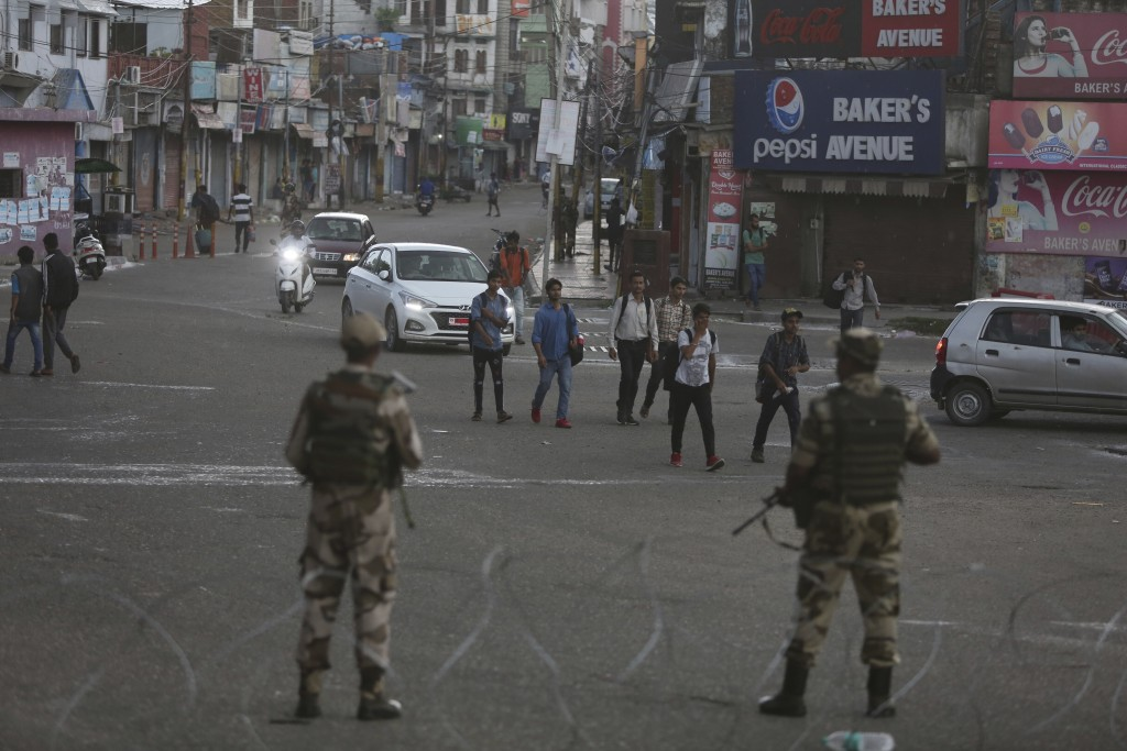 Indian paramilitary soldiers stand guard during curfew like restrictions in Jammu, India, Monday, Aug. 5, 2019. An indefinite security lockdown was in...
