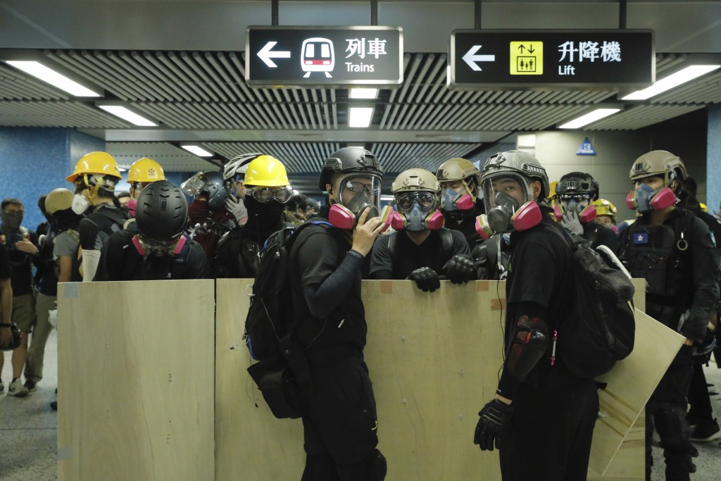 Protesters with makeshift shields pass through a subway station on their way to a police station in Hong Kong on Sunday, Aug. 4, 2019. Demonstrators i...