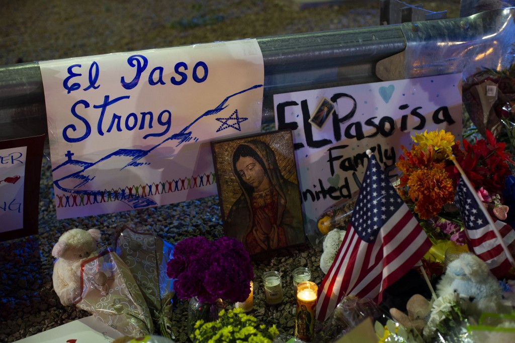 A Virgin Mary painting, flags and flowers adorn a makeshift memorial for the victims of Saturday's mass shooting at a shopping complex in El Paso, Tex