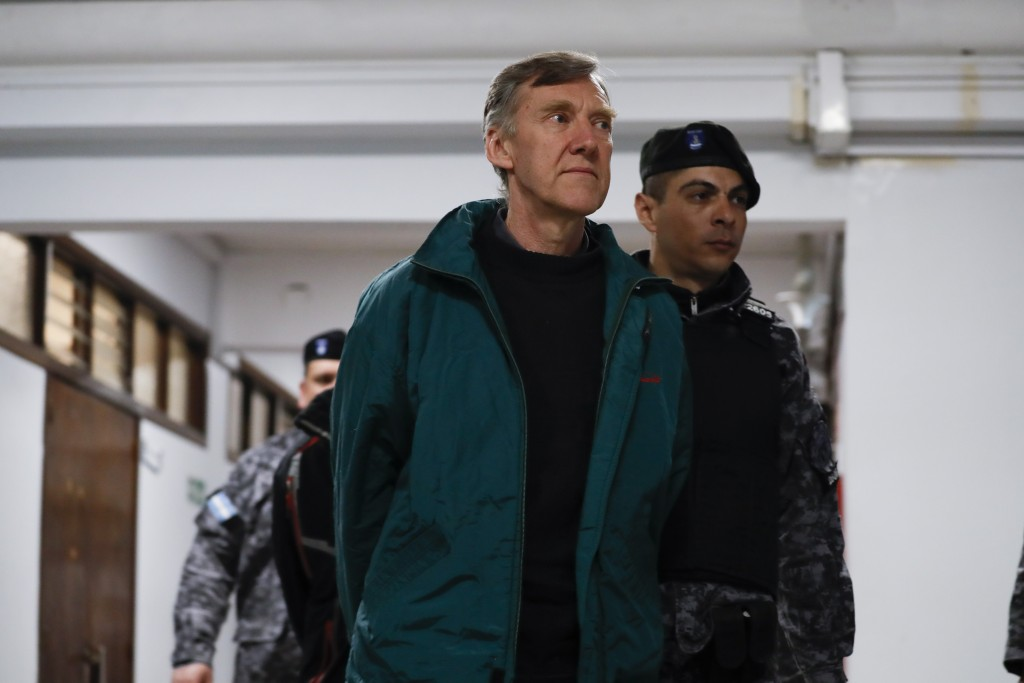 Rev. Horacio Corbacho is escorted from a courtroom after attending his trial in Mendoza, Argentina, Monday, Aug. 5, 2019. Corbacho is charged with all