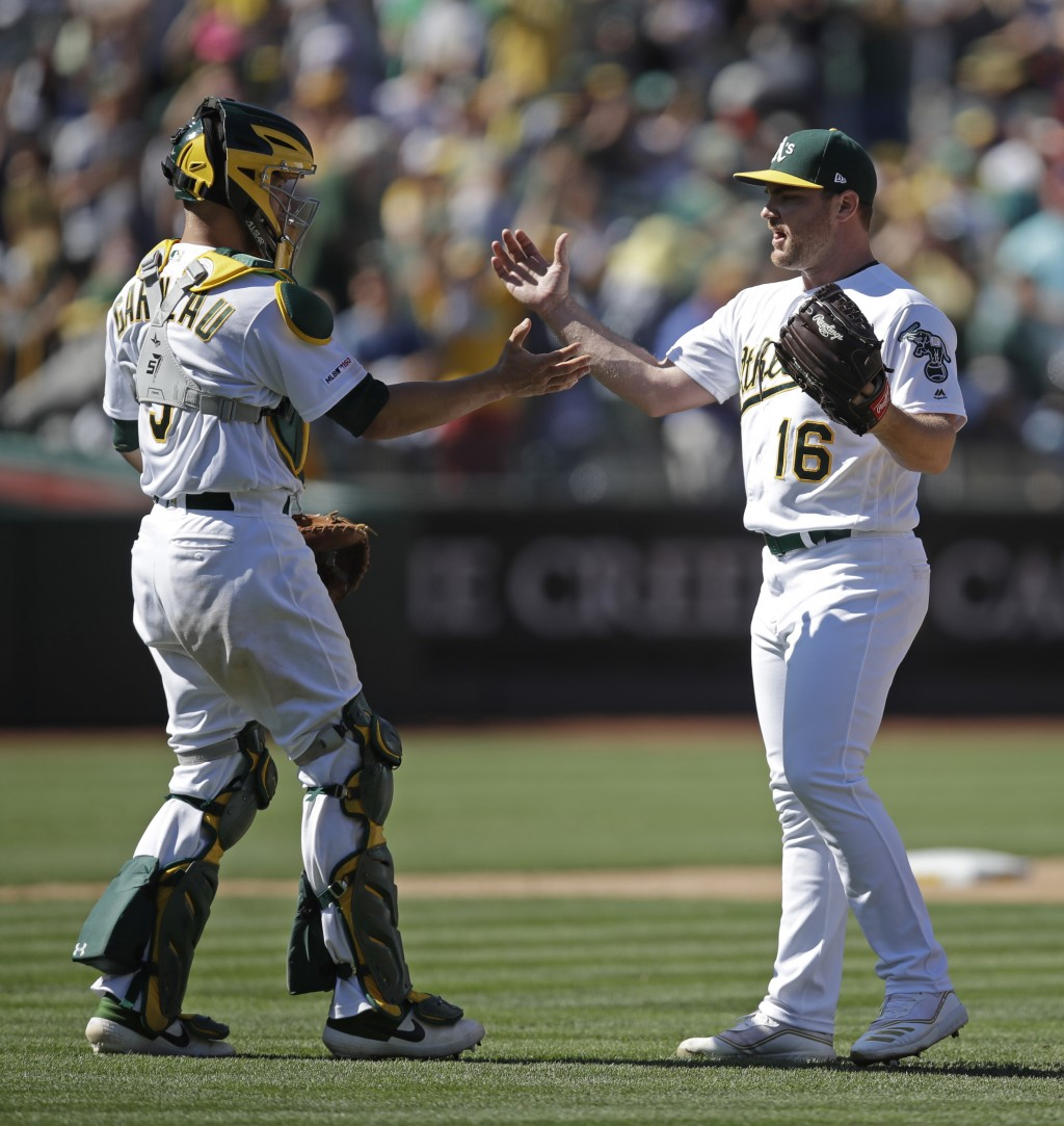 Oakland Athletics pitcher Liam Hendriks, right, and Dustin Garneau celebrate the 4-2 win over the St. Louis Cardinals at the end of a baseball game Su