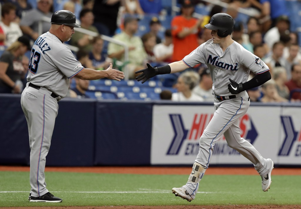 Miami Marlins' Brian Anderson, right, shakes hands with third base coach Fredi Gonzalez after hitting a solo home run off Tampa Bay Rays relief pitche
