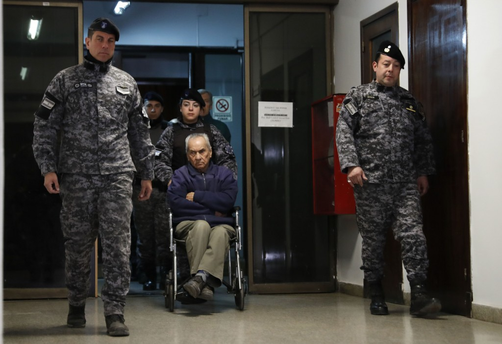 Rev. Nicola Corradi, in wheelchair, is escorted to a courtroom to attend his trial in Mendoza, Argentina, Monday, Aug. 5, 2019. In late November 2016,