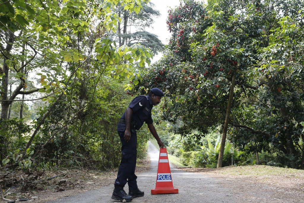A police officer sets up a cone at the entrance of The Dusun resort where a 15-year-old London schoolgirl went missing, in Seremban, Negeri Sembilan,