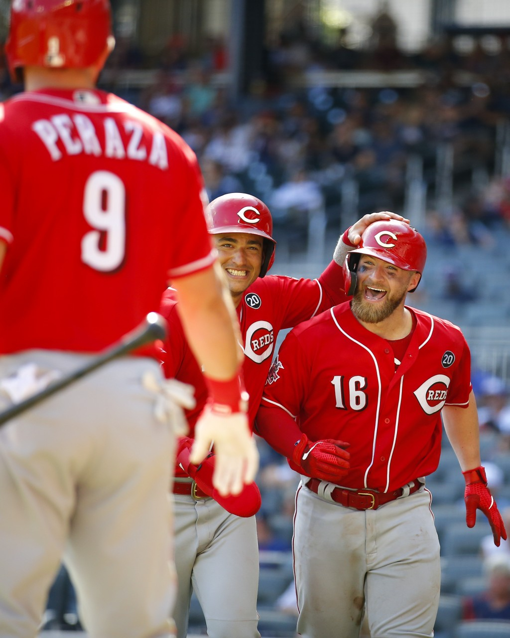 Cincinnati Reds' Tucker Barnhart (16) reacts with Jose Iglesias and Jose Peraza after hitting a three-run home run in the tenth inning of a baseball g...