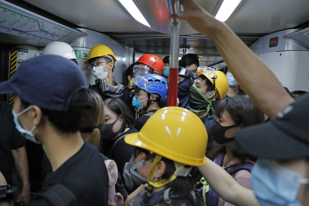 Protesters with protective gear take a train to the anti-extradition bill protest destination, in Hong Kong on Sunday, Aug. 4, 2019. Demonstrators in ...