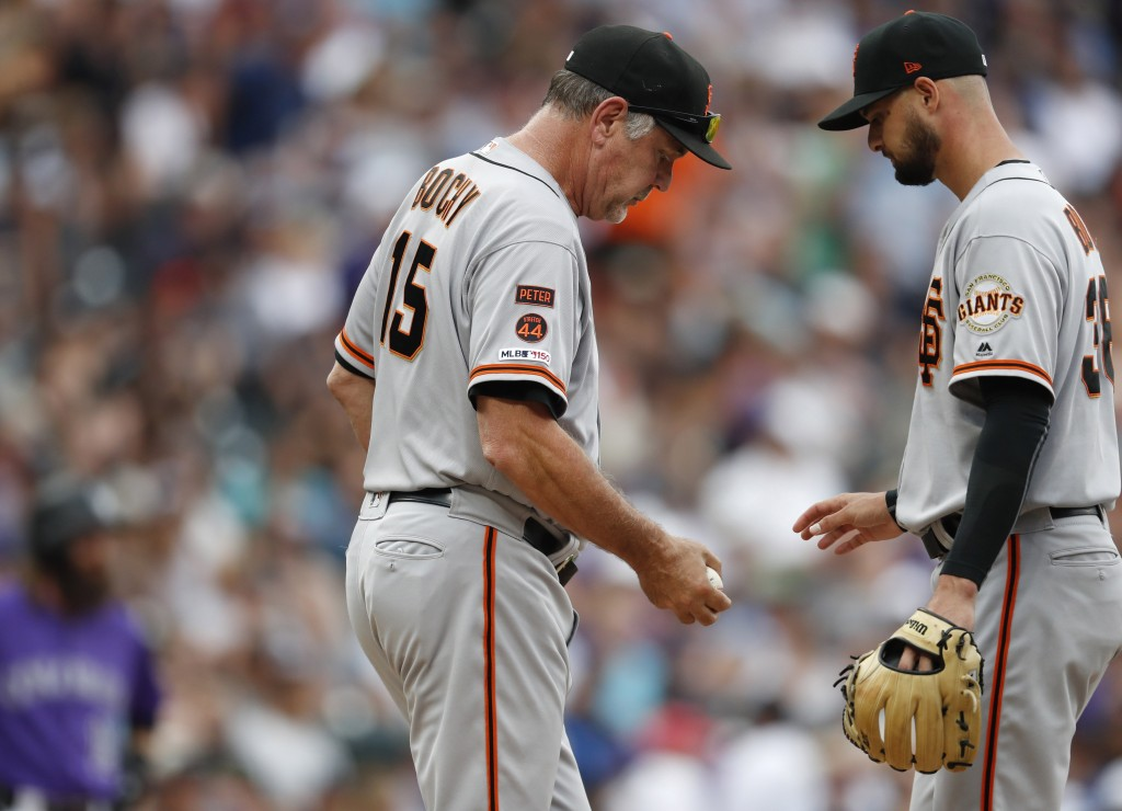 San Francisco Giants manager Bruce Bochy, left, takes the ball from starting pitcher Tyler Beede who is pulled from the mound after giving up a double...