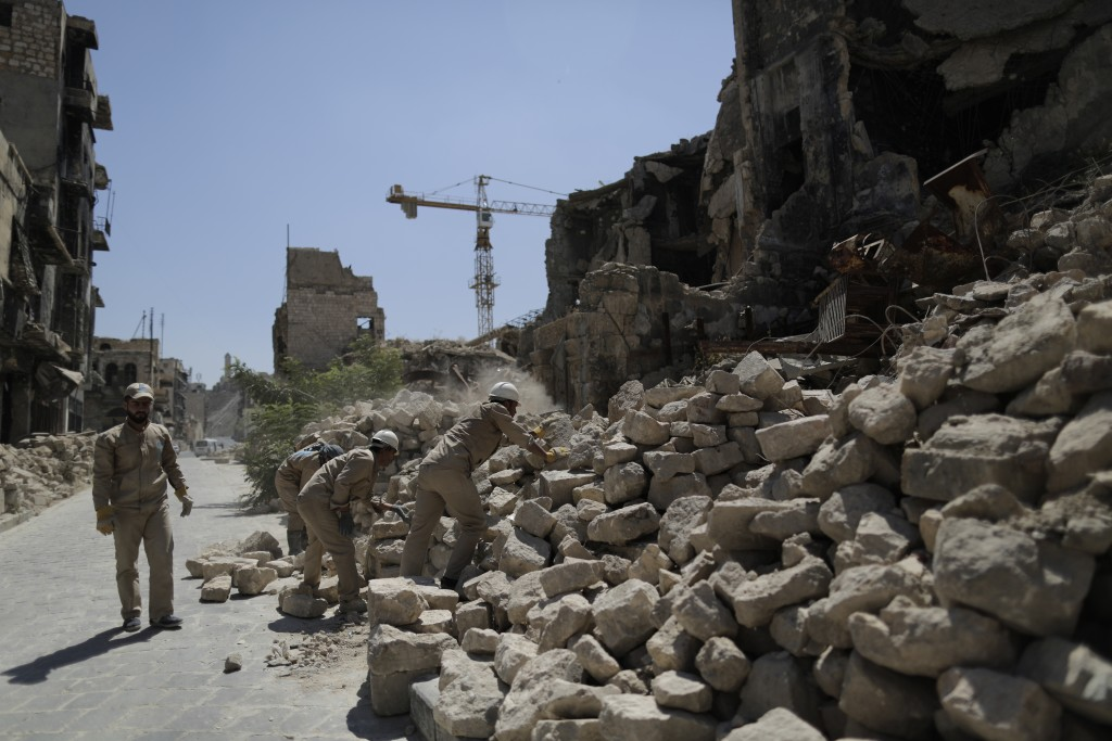 In this Saturday, July 27, 2019 photo, Syrian workers remove rubble from damaged shops in the old city of Aleppo, Syria. Much of Aleppo's centuries-ol