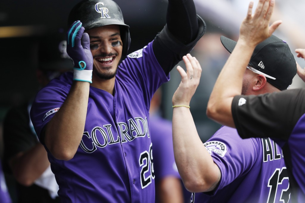 Colorado Rockies' Nolan Arenado celebrates with teammates as he returns to the dugout after hitting a solo home run off San Francisco Giants starting ...