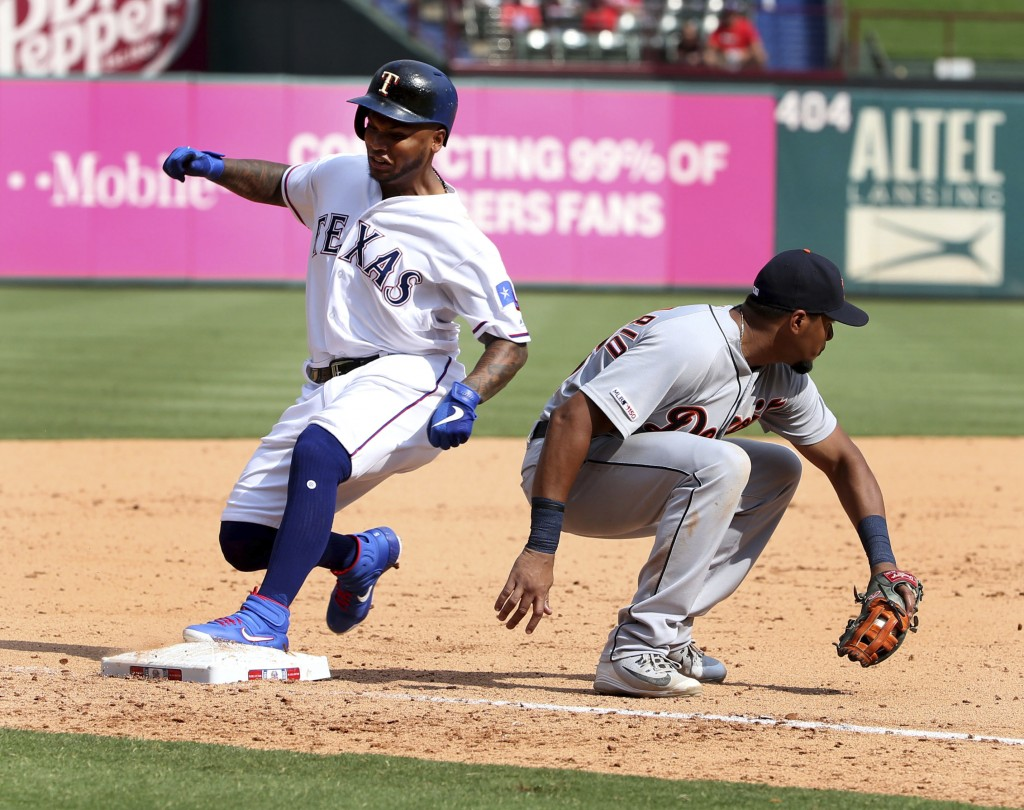 Texas Rangers Willie Calhoun, left, gets to third in front of Detroit Tigers third baseman Jeimer Candelario, right, for a three-run triple during the...