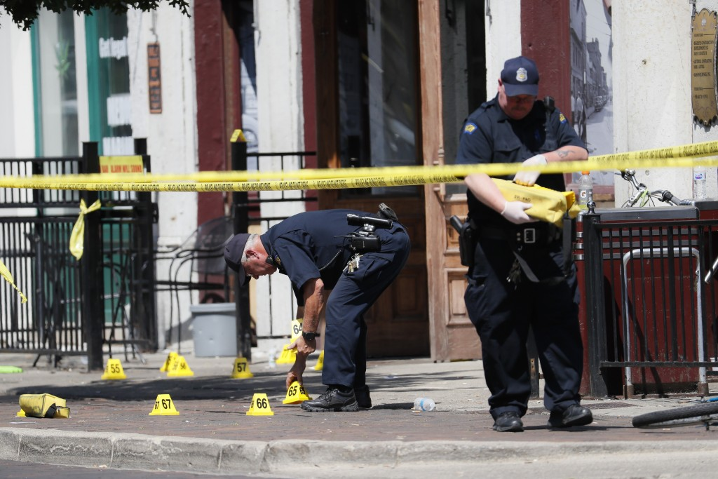 Authorities retrieve evidence markers at the scene of a mass shooting, Sunday, Aug. 4, 2019, in Dayton, Ohio. Multiple people in Ohio have been killed...