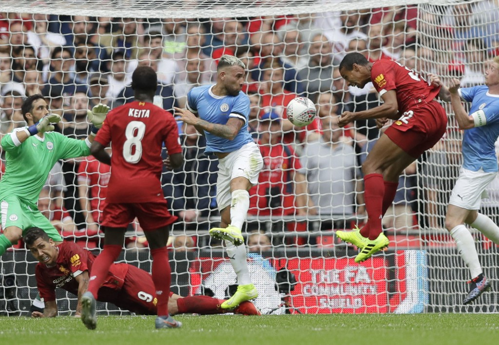 Liverpool's Joel Matip, second from right, scores his side's first goal during the English Community Shield soccer match between Liverpool and Manches