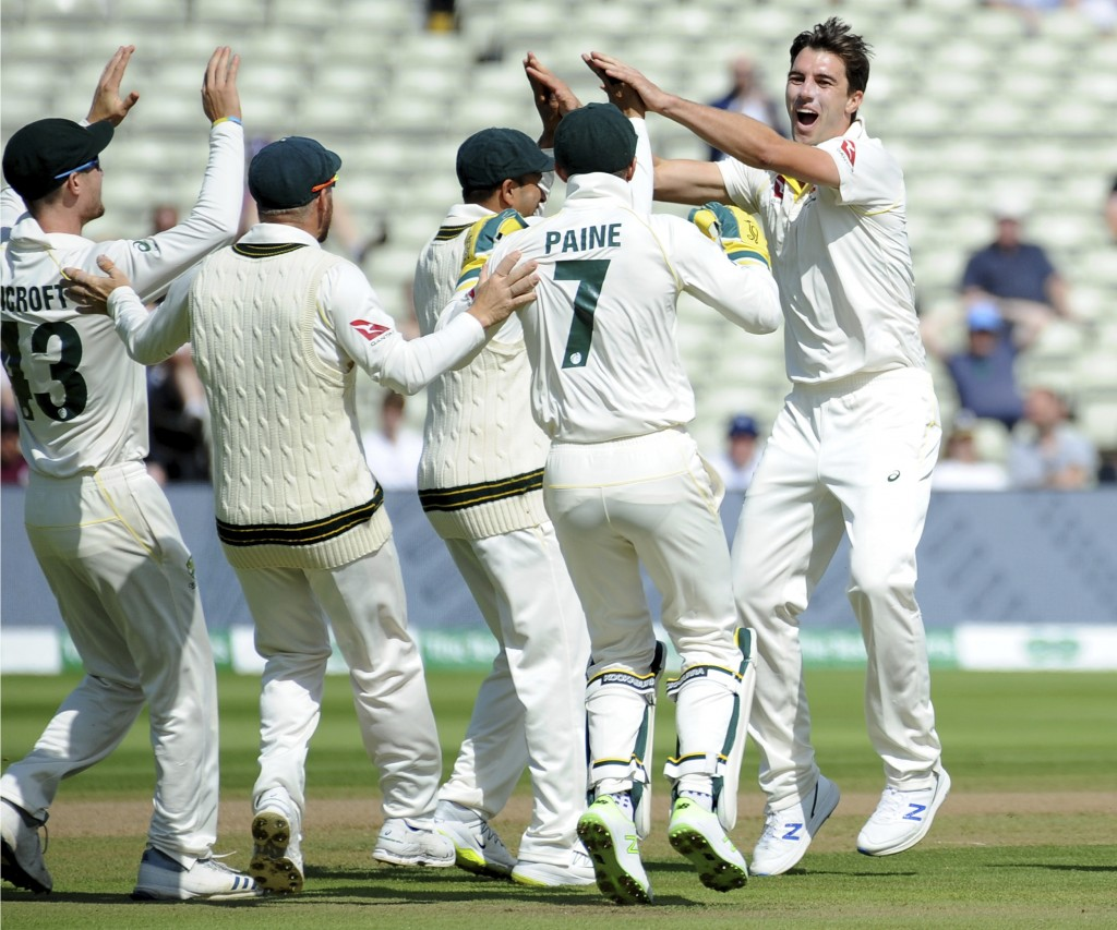 Australia's Pat Cummins, right, celebrates with teammates after dismissing England's Rory Burns on day five of the first Ashes Test cricket match betw...