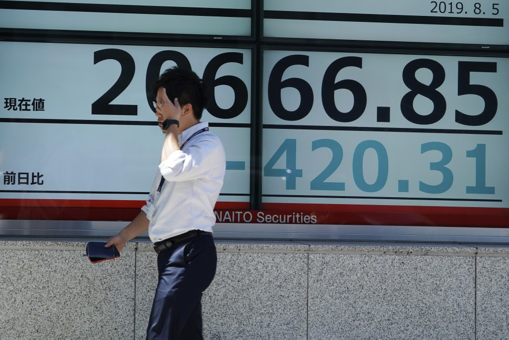 A man walks past an electronic stock board showing Japan's Nikkei 225 index at a securities firm in Tokyo Monday, Aug. 5, 2019. Asian stock markets fe...