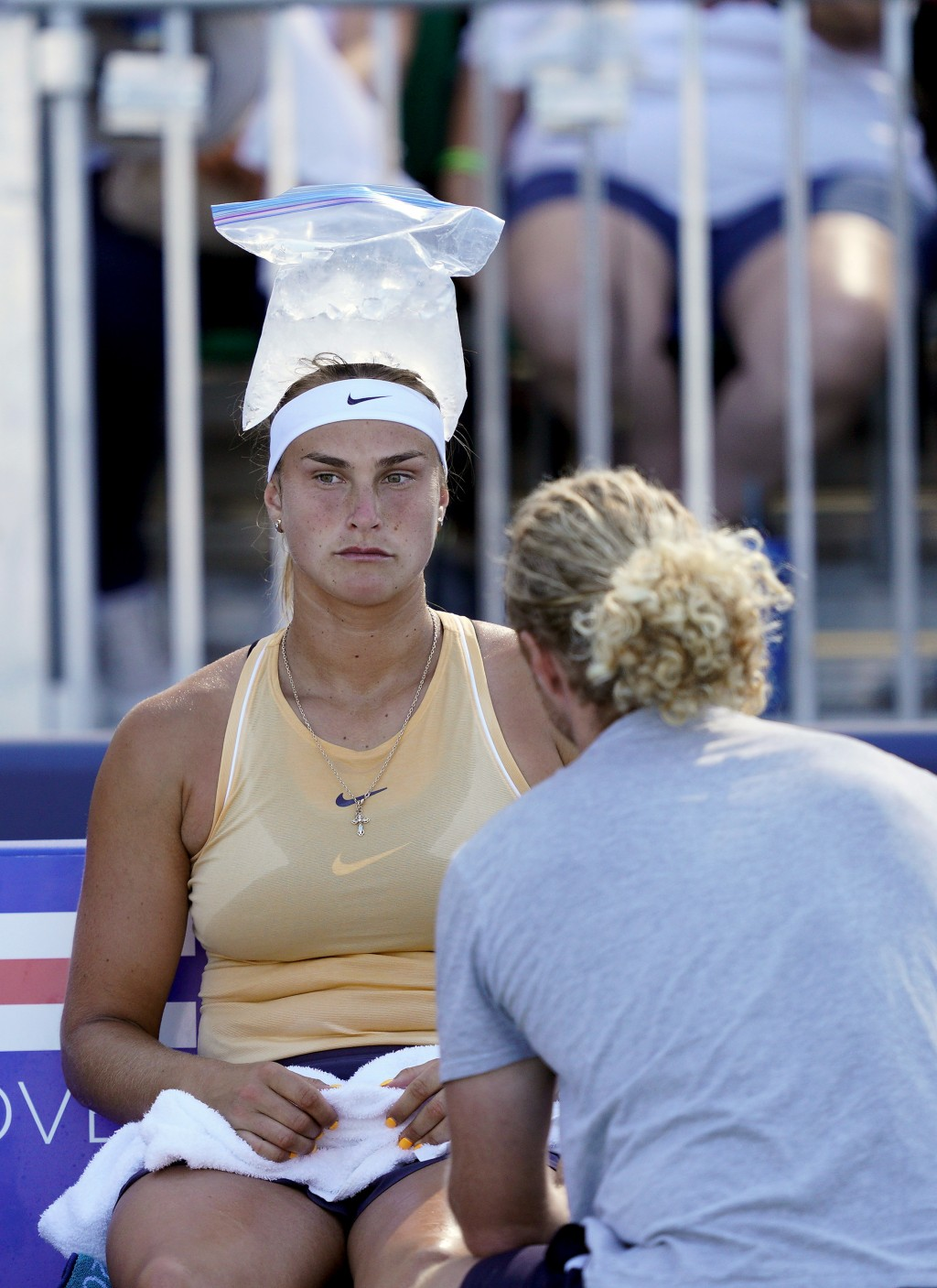 Aryna Sabalenka, of Belarus, uses a bag of ice on her head to cool off as she talks to her coach during a break in the match against Zheng Saisai, of