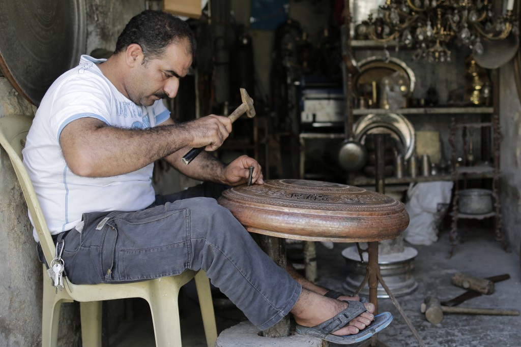 In this Sunday, July 28, 2019 photo, Ahmad Zuhdi Ghazoul works on a piece of copper on the newly renovated copper market in Aleppo, Syria. Much of Ale