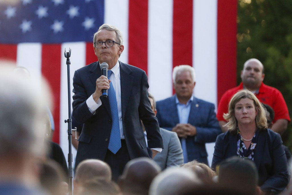 Ohio Gov. Mike DeWine, left, speaks alongside Dayton Mayor Nan Whaley, right, during a vigil at the scene of a mass shooting, Sunday, Aug. 4, 2019, in