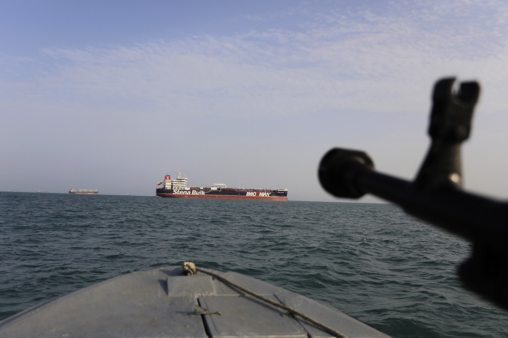 FILE - In this In this July 21, 2019 file photo, a speedboat of Iran's Revolutionary Guard trains a weapon toward the British-flagged oil tanker Stena...