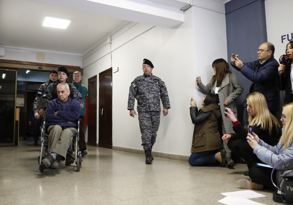 Rev. Nicola Corradi, in wheelchair, and and Rev. Horacio Corbacho, following behind in green, are escorted to a courtroom to attend their trial in Men...