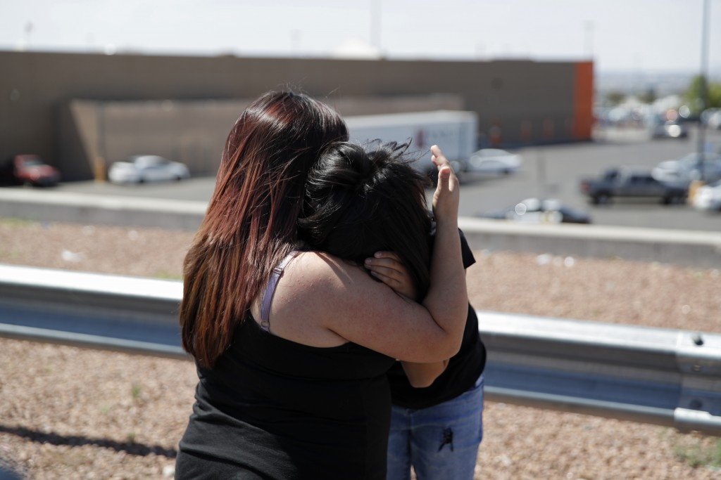 Eleven-year-old Leilani Hebben, right, embraces her mother Anabel Hebben as they visit the scene of a mass shooting at a shopping complex Sunday, Aug.