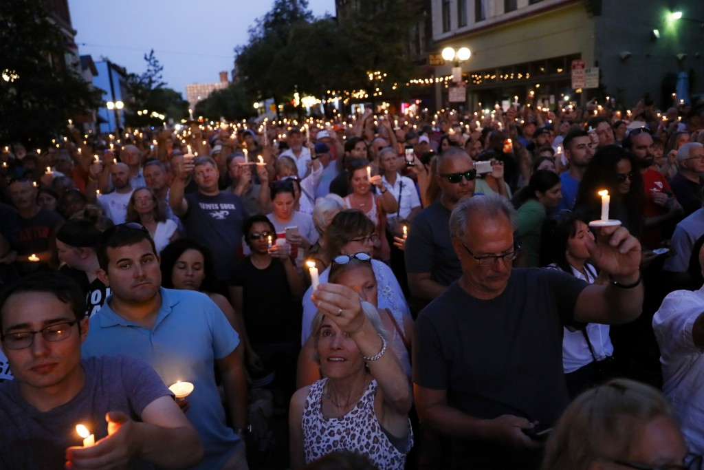 Mourners gather for a vigil at the scene of a mass shooting, Sunday, Aug. 4, 2019, in Dayton, Ohio. Multiple people in Ohio were killed in the second