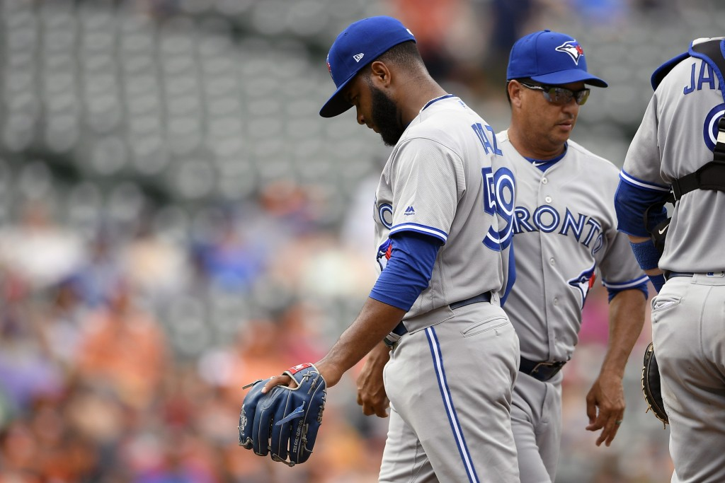 Toronto Blue Jays' relief pitcher Yennsy Diaz, left, is pulled from a baseball game by manager Charlie Montoyo, right, during the fifth inning against...