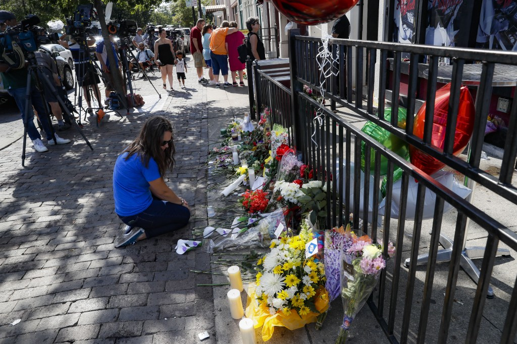 "A mourner kneels at a makeshift memorial near a members of the media outside the ""Hole in the Wall"" bar in the Oregon District, Monday, Aug. 5, 2019,"