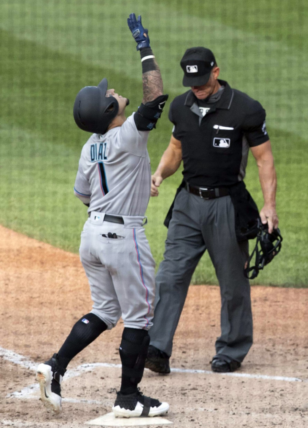 Miami Marlins' Isan Diaz, left, reacts as he comes into home plate after hitting a home run in his major league debut during the sixth inning of a bas...