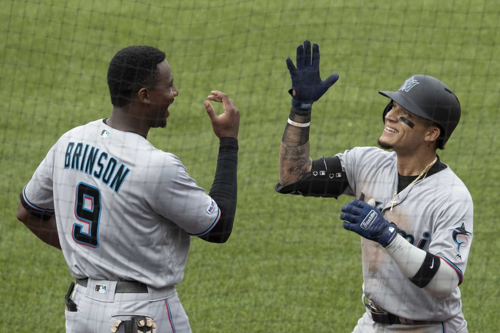 Miami Marlins' Isan Diaz, right, celebrates after hitting a home run in his major league debut with Lewis Brinson (9) during the sixth inning of a bas...