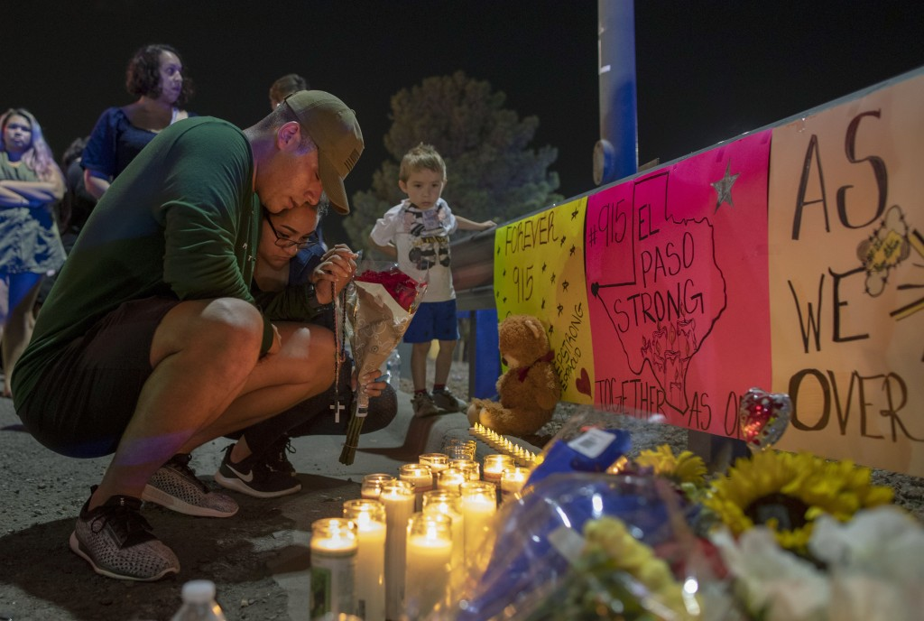 FILE - In this Aug. 4, 2019, file photo, Rene Aguilar and Jackie Flores pray at a makeshift memorial for the victims of Saturday's mass shooting at a ...