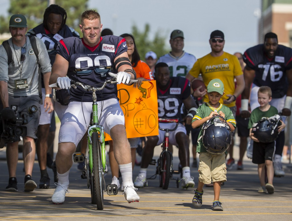 Houston Texans' J.J. Watt rides a bike to a joint NFL football practice between the Texans and the Green Bay Packers Monday, Aug 5, 2019, in Green Bay...