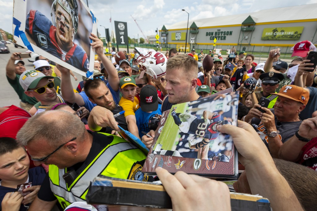 Houston Texans' J.J. Watt signs autographs after a joint NFL football practice with the Green Bay Packers Monday, Aug 5, 2019, in Green Bay, Wis. (AP ...