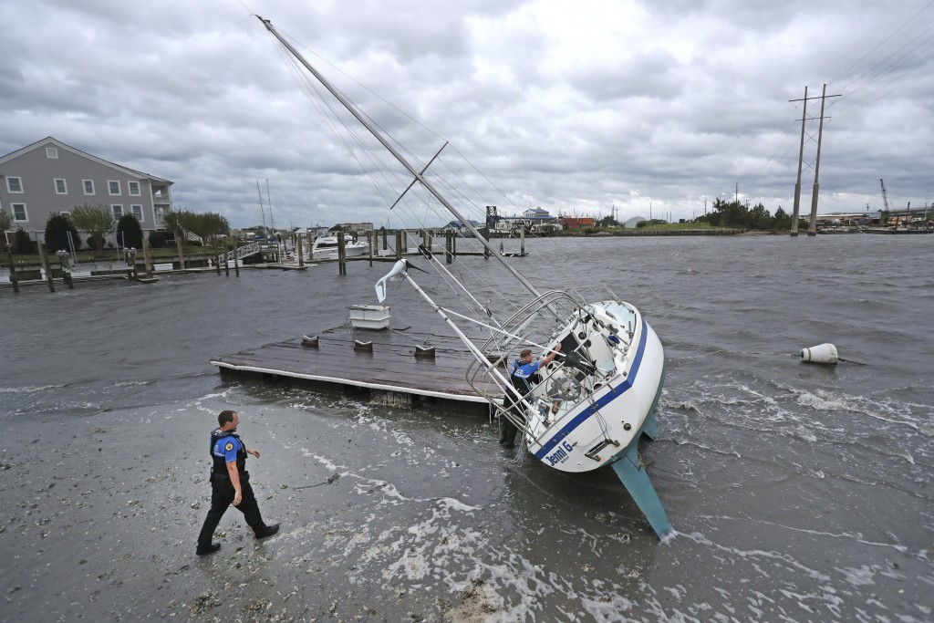 Beaufort Police Officer Curtis Resor, left, and Sgt. Micheal Stepehens check a sailboat for occupants in Beaufort, N.C. after Hurricane Dorian passed ...