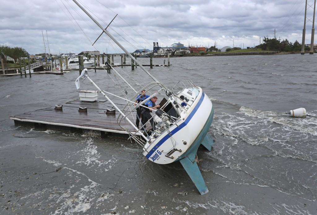 Beaufort Police Officer Curtis Resor, left, and Sgt. Micheal Stepehens check a sailboat for occupants in Beaufort, N.C. after Hurricane Dorian passed
