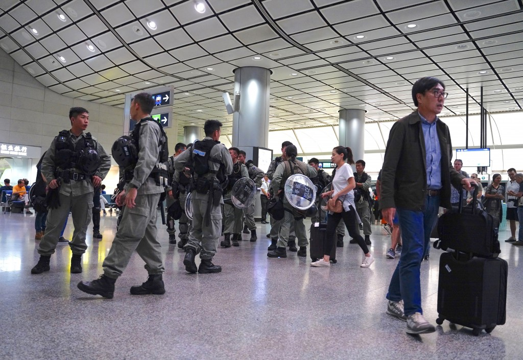 Riot police stand guard at the airport express central station in downtown Hong Kong, Saturday, Sept. 7, 2019. Hong Kong authorities were limiting air
