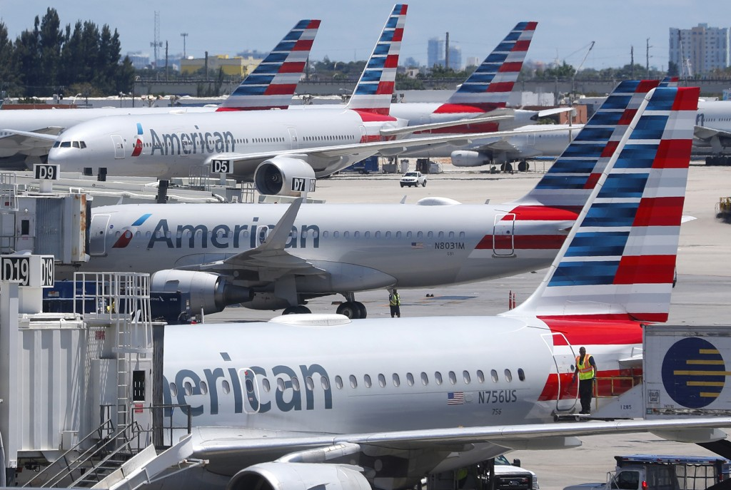 FILE - In this April 24, 2019, photo, American Airlines aircraft are shown parked at their gates at Miami International Airport in Miami. An American ...