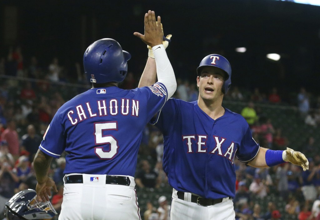 Texas Rangers' Willie Calhoun (5) greets Nick Solak at the plate after the latter's two-run home run against the Tampa Bay Rays during the fourth inni...